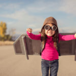 A young girl is wearing goggles and a flight cap and is ready to take to the sky. She has made her own jet pack and is ready to fly away to her dreams. The girl is standing on a road in rural Utah, USA. Girls have big ideas too.